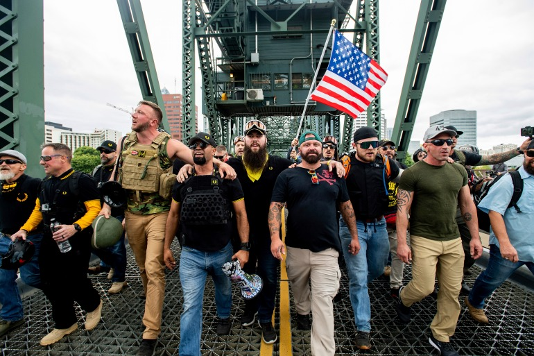 Members of the Proud Boys and other right-wing demonstrators march across the Hawthorne Bridge during a rally in Portland [File: Noah Berger/AP]