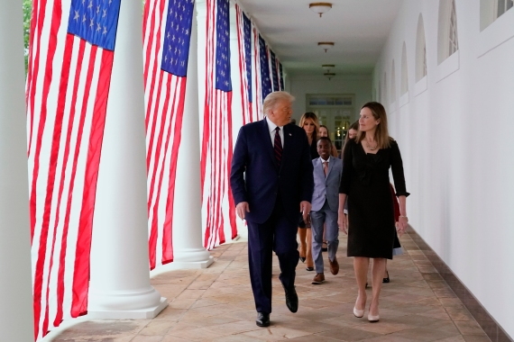 United States President Donald Trump walks along the White House Colonnade with Judge Amy Coney Barrett, his nominee to the Supreme Court [Alex Brandon/the Associated Press]