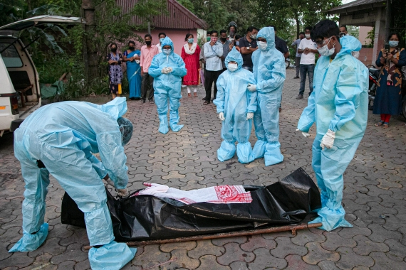 Healthcare workers show the body of someone who died of COVID-19 to relatives in Gauhati, India [Anupam Nath/AP]
