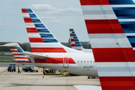 A member of a ground crew walks past American Airlines planes parked at the gate during the coronavirus outbreak at Ronald Reagan National Airport in Washington, United States [File: Joshua Roberts/Reuters]