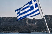 A naval vessel patrols off the tiny Greek island of Kastellorizo in front of a Greek flag, 2km from the Turkish mainland [Louisa Gouliamaki/AFP]