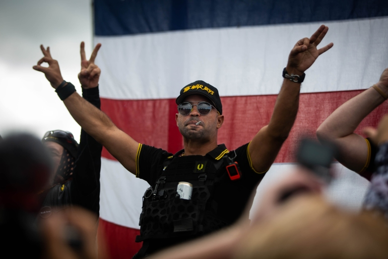 A man at a Proud Boys rally wearing a yellow-and-black shirt gestures the OK sign that is now seen as a symbol of white supremacy [Maranie R Staab/AFP]