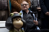 Argentine cartoonist Joaquin Salvador Lavado, better known as Quino, poses for a photo with a statue of Mafalda during a 50th anniversary celebration, in Buenos Aires, Argentina [File: Eduardo Di Baia/AP Photo]