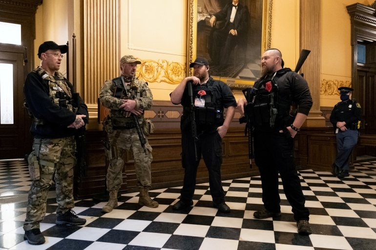 Members of a militia stand in the Capitol Hill building in Lansing, Michigan on April 30, 2020 [Seth Herald/Reuters]