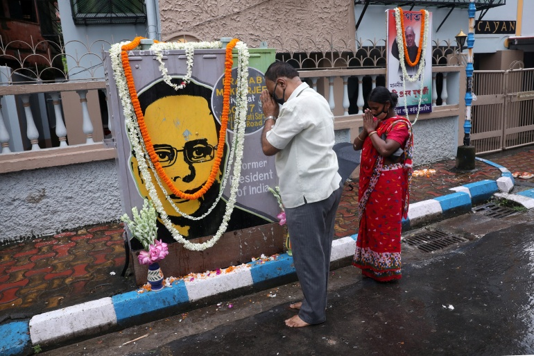 People pray in front of a painting of India's former President Pranab Mukherjee, in Kolkata, September 1, 2020 [File: Rupak De Chowdhuri/Reuters]