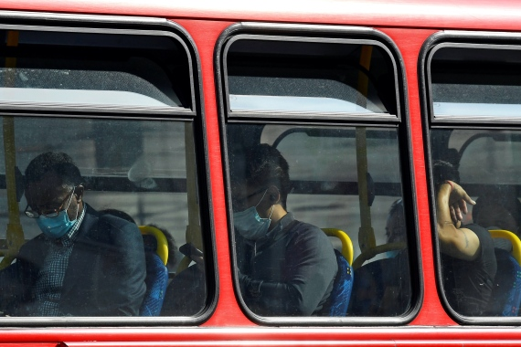 Passengers wear protective face coverings on a bus in London, United Kingdom, where the government is trying to prevent widespread layoffs [File: Toby Melville/Reuters]