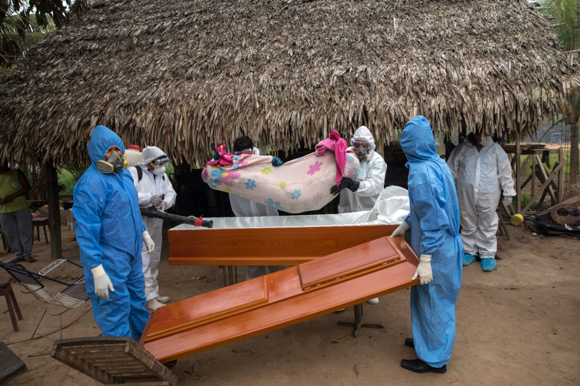 A government team removes the body of Manuela Chavez, who died from symptoms related to the new coronavirus at the age of 88, from inside her home and places her in a casket, in the Shipibo Indigenous community of Pucallpa. [Rodrigo Abd/AP Photo]