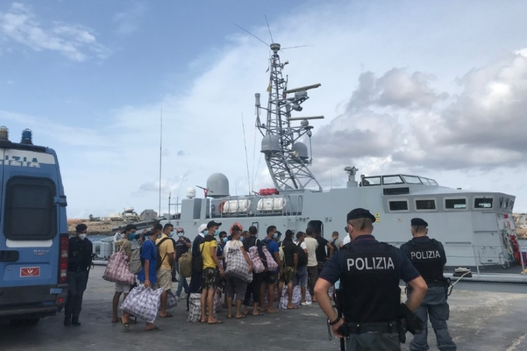 Refugees and migrants queue to board an Italian coastguard vessel which will take them to a ferry, where they will start a two-week quarantine period [Al Jazeera]