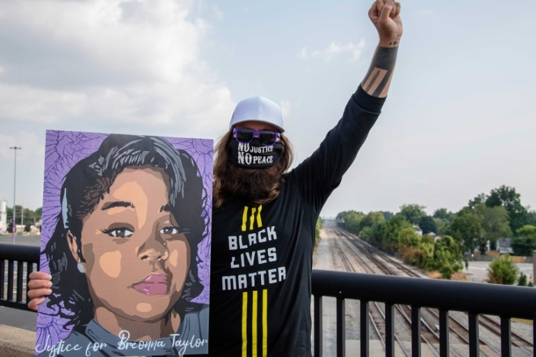 A protester holding a picture of Breonna Taylor in Louisville, Kentucky [Amy Harris/Invision/AP]