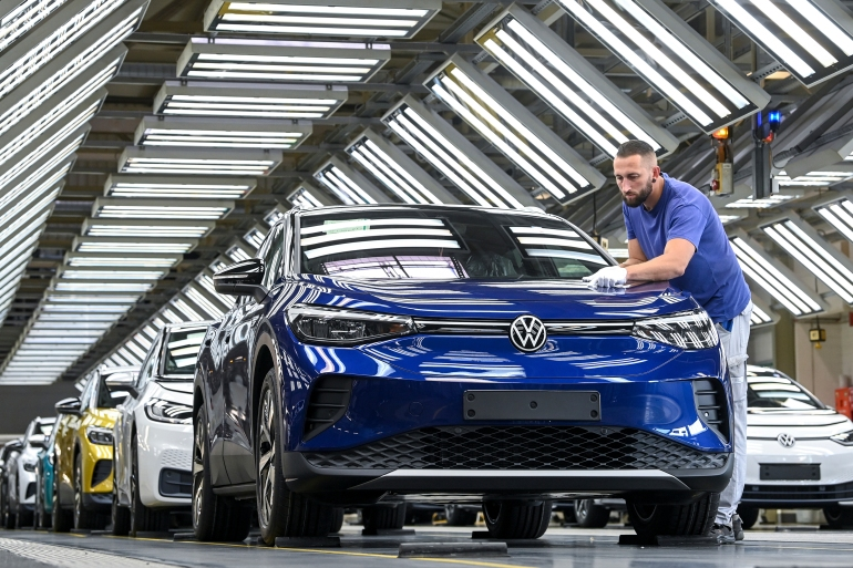 An employee puts the finishing touches to a battery-powered VW ID.4 at the Volkswagen plant in Zwickau, Germany [File: Hendrik Schmidt/DPA via AP Photo]