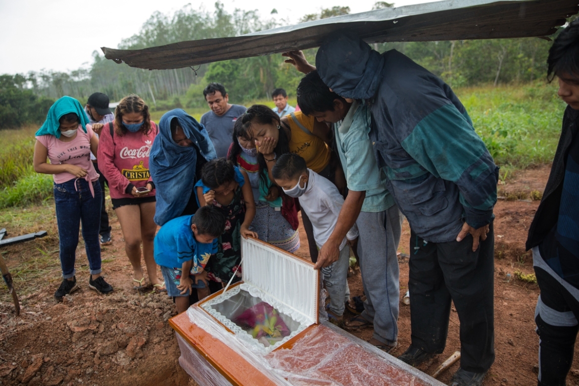 Family members look in Manuela Chavez's coffin, during a burial service in the Shipibo Indigenous community of Pucallpa. Manuela died from symptoms related to the coronavirus. [Rodrigo Abd/AP Photo]