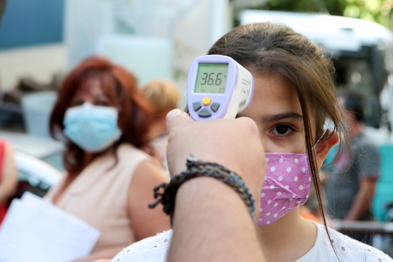 A student gets her temperature checked during the beginning of the new school year in Athens, Greece, 14 September 2020.  EPA-EFE/PANTELIS SAITAS [EPA]