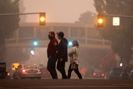 Residents crossing a street as smoke from wildfires covers an area near Salem, Oregon [Carlos Barria/Reuters]