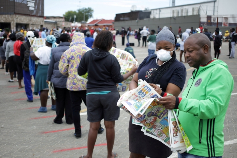 Shoppers queue outside a grocery store back in March during an initial 21-day nationwide lockdown aimed at limiting the spread of the novel coronavirus in Soweto, South Africa [File: Siphiwe Sibeko/Reuters]