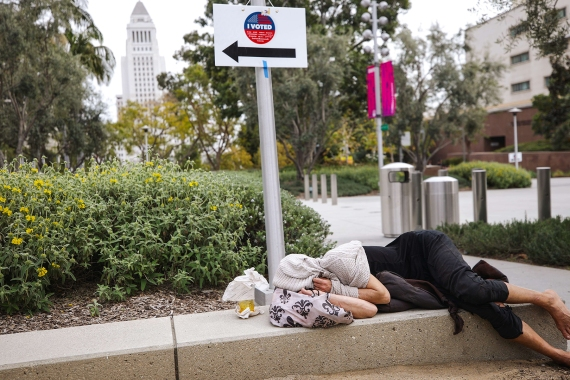 A woman sleeps beneath a sign pointing to a new Mobile Vote Center during early voting for the California presidential primary election on February 27, 2020 in Los Angeles, California [Mario Tama/Getty Images/AFP]