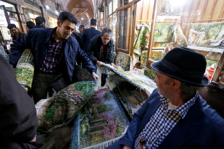 A picture taken on April 24, 2018 shows Iranians shopping for carpets at the Bazaar in Tabriz in Iran's northwestern East-Azerbaijan province [Atta Kenare/AFP]