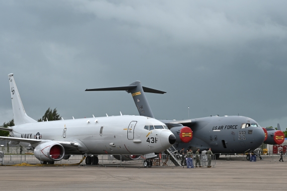 Visitors stand next to a static US Navy aircraft the Poseidon P-8, left, and the USAF Boeing C-17A Globemaster III, right, on the tarmac during the Singapore Airshow in Singapore on February 11, 2020 [File: Roslan Rahman/AFP]