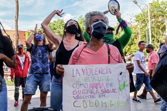 Women protest against violence against women with a sign reading 'Sexual violence as a war weapon still exists in Colombia' in Medellin, Colombia, on June 19, 2020, amid the new coronavirus pandemic [Photo by Joaquin Sarmiento/AFP]