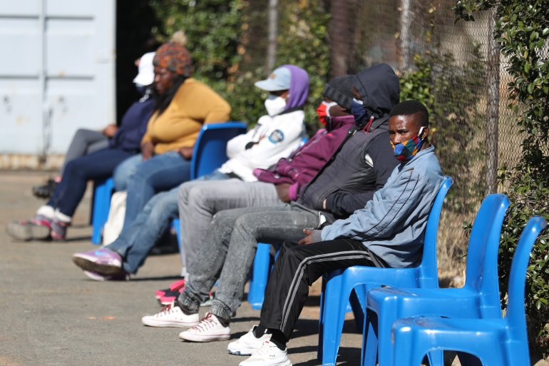 Some of the first South African COVID-19 vaccine trialists wait outside a clinic in Soweto [Siphiwe Sibeko/AFP]