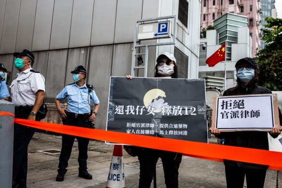 Family members of some of the 12 Hong Kong residents arrested in mainland China after they were caught trying to flee to Taiwan hold a protest outside the Chinese Liaison office [Isaac Lawrence/AFP]