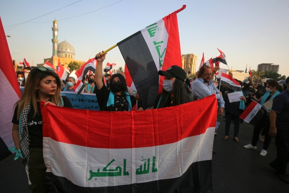 Iraqis carry national flags as they demonstrate in the capital Baghdad's Al-Firdous Square during the commemoration of the first anniversary of anti-government protest movement against unemployment, poor public services, and endemic corruption [Ahmad al-Rubaye/AFP]