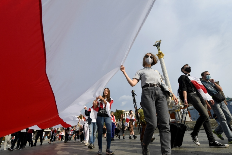 Members of the Belarusian diaspora carry a giant former Belarus white-red-white flag on October 4, 2020 during a rally on Independence Square in Kiev demanding to free jailed opposition activists [Photo by Sergei Supinsky / AFP]