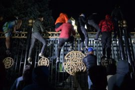 Protesters attempt early on Tuesday to break through the gates of the government headquarters during a rally against the results of a parliamentary vote in Bishkek [Vyacheslav Oseledko/AFP]