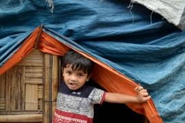 A Rohingya refugee child looks from his makeshift shanty at Kutupalong refugee camp, Cox's Bazar [File: Munir Uz Zaman/AFP]