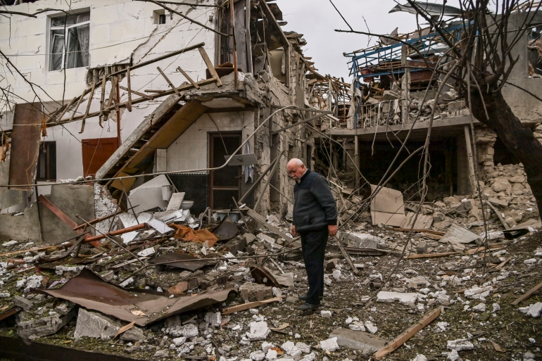 An elderly man stands in front of a destroyed house after shelling in the breakaway Nagorno-Karabakh region's main city of Stepanakert on October 7, 2020 [Aris Messinis/AFP]