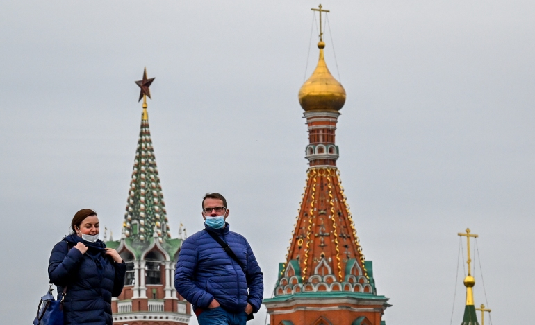 A man and a woman wearing face masks to protect against the coronavirus disease walk at the Zaryadye park, with the Kremlin's Spasskaya tower and St Basil's cathedral on the background, in central Moscow [File: Yuri Kadobnov/AFP]
