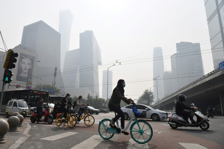 People cross a road on a polluted day in Beijing on October 10, 2020 [Greg Baker/ AFP]