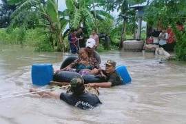 Soldiers pull a woman to safety from floodwaters in a village in Cambodia's western Battambang province on October 10, 2020, following heavy rains in the region [Photo by STR/AFP]