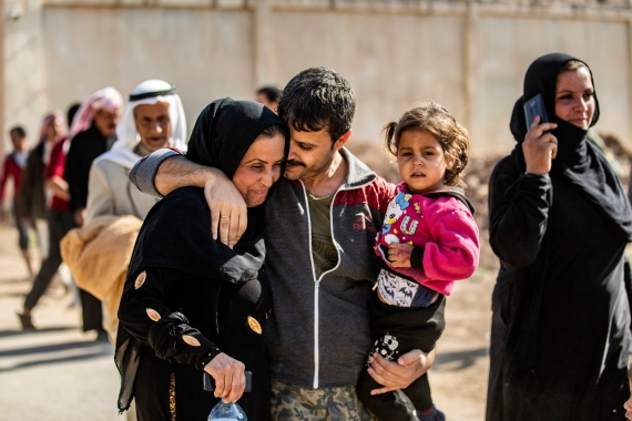 A man suspected of having collaborated with ISIL is greeted by family members upon his release from the Kurdish-run Alaya prison in the northeastern Syrian city of Qamishli [Delil Souleiman/AFP]