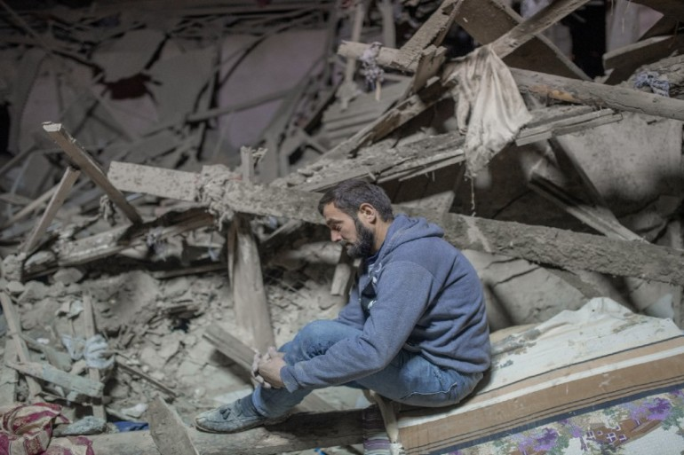 A resident sits amid the rubble awaiting the search for his relatives as rescue teams work at a site hit by a rocket during fighting over the breakaway region of Nagorno-Karabakh, in the city of Ganja, Azerbaijan early on October 17, 2020 [File: Bulent Kilic/AFP]