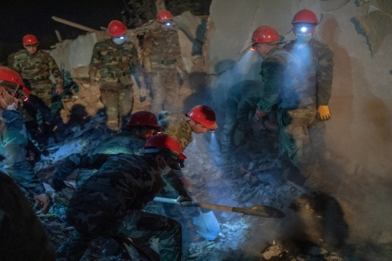 Rescue teams sift through rubble at a site in the city of Ganja, Azerbaijan [Bulent Kilic/AFP]
