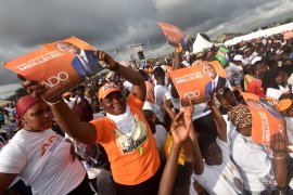Supporters of incumbent President Alassane Ouattara take part in a campaign meeting in Abidjan ahead of the presidential election [Sia Kambou/AFP]