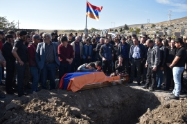 People mourn by the coffin of Armenian soldier Samvel Hovakimyan, 23, who was killed in the fighting between Armenia and Azerbaijan over the breakaway region of Nagorno-Karabakh, during a funeral ceremony at a cemetery in the town of Gyumri on October 19, 2020 [Karen Minasyan/AFP]