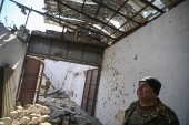 The mayor of the city of Martakert stands inside a building destroyed by shelling in Martakert [Aris Messinis/AFP]