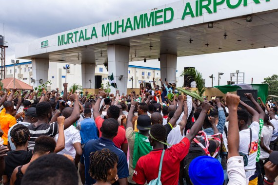 Protesters hold a minute of silence to honour victims of police brutality at the Murtala Muhammed airport during ongoing protests. [Benson Ibeabuchi/AFP]
