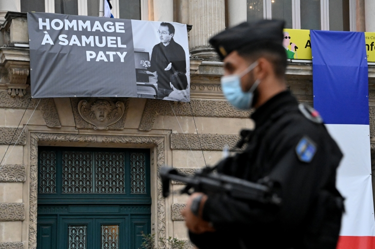 A French police officer stands next to a portrait of French teacher Samuel Paty on display on the facade of the Opera Comedie in Montpellier on October 21, 2020, during a national homage [Pascal Guyot/AFP]
