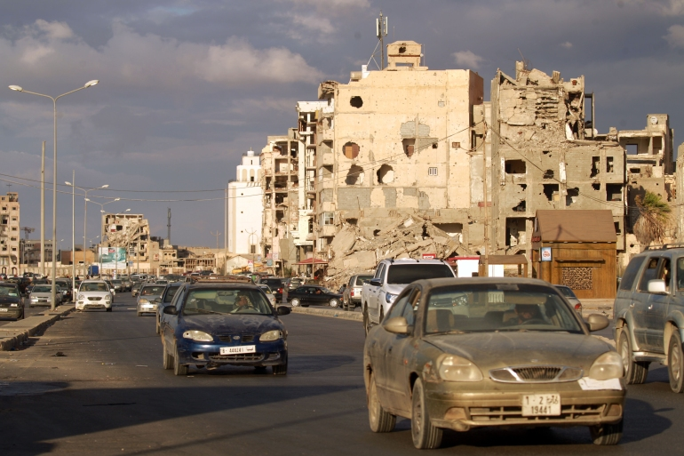 Cars drive near shell-pocked buildings in Libya's eastern coastal city of Benghazi after a ceasefire agreement was signed [Abdullah Doma/AFP]