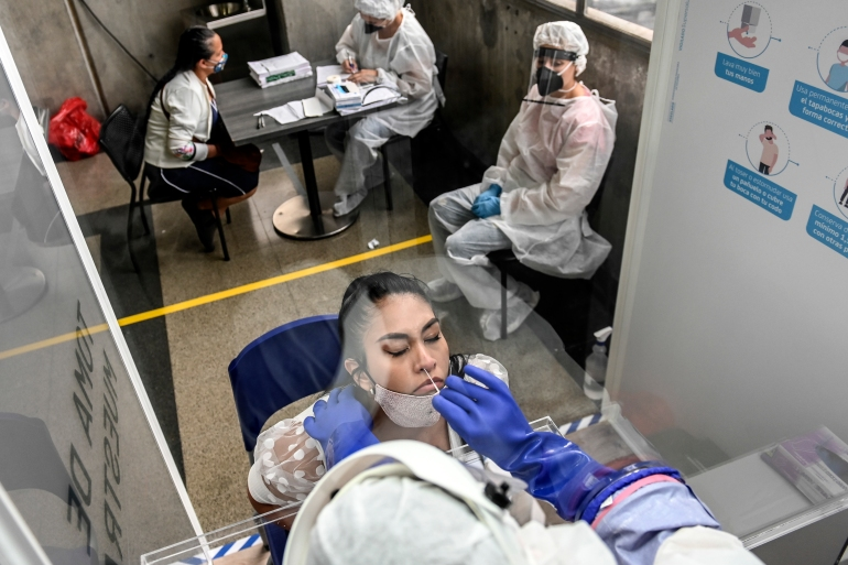 A woman is tested for COVID-19 during a random testing at a Metro station, amid the coronavirus pandemic, in Medellin, Colombia [File: Joaquin Sarmiento/ AFP]