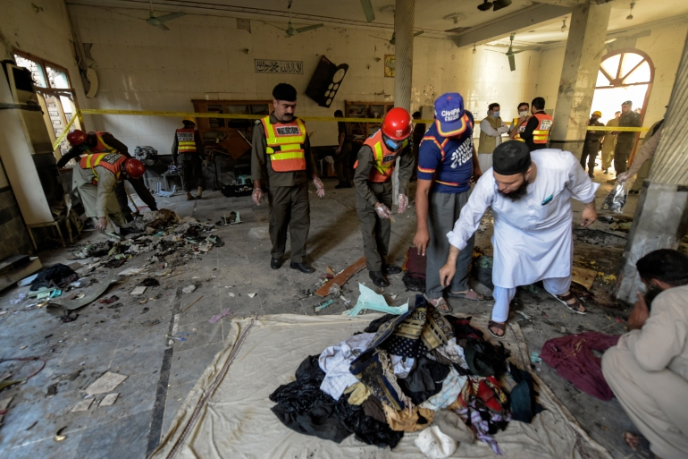 Rescue workers collect the remains of victims after a blast at a religious school in Peshawar [Abdul Majeed/AFP]