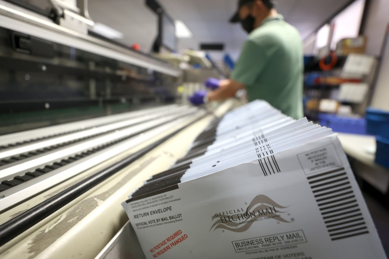 Mail-in ballots sit in a sorting machine at the Santa Clara County registrar of voters' office on October 13, 2020 in San Jose, California. The Santa Clara County registrar of voters is preparing to process thousands of ballots as early voting gets under way in the state of California [Justin Sullivan/Getty Images/AFP]