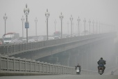 People ride along a bridge on a smoggy day in Nanjing, Jiangsu province in China [File: Reuters]
