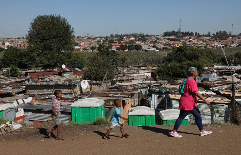 A mother and her children walk past public toilets at an informal settlement in Kliptown, Soweto. South Africa is considered a middle-income country and will not qualify for cheaper COVID-19 vaccines [Reuters/Siphiwe Sibeko]