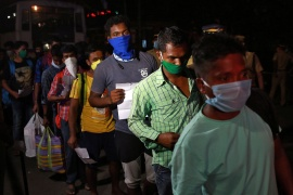Migrant workers stranded in Kerala due to a COVID-19 lockdown arrive at a railway station in Kochi to leave for their home state of eastern Odisha [File: Sivaram V/Reuters]