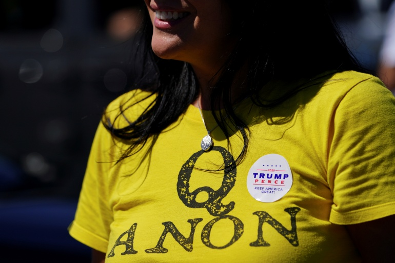 A supporter of US President Donald Trump wears a QAnon shirt after participating in a caravan convoy circuit in Adairsville, Georgia [File: Elijah Nouvelage/Reuters]