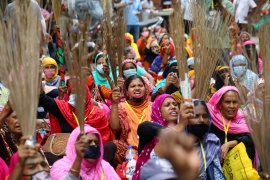 Garment workers shout slogans while holding brooms during a protest demanding their due wages in Dhaka last month [Mohammad Ponir Hossain/Reuters]