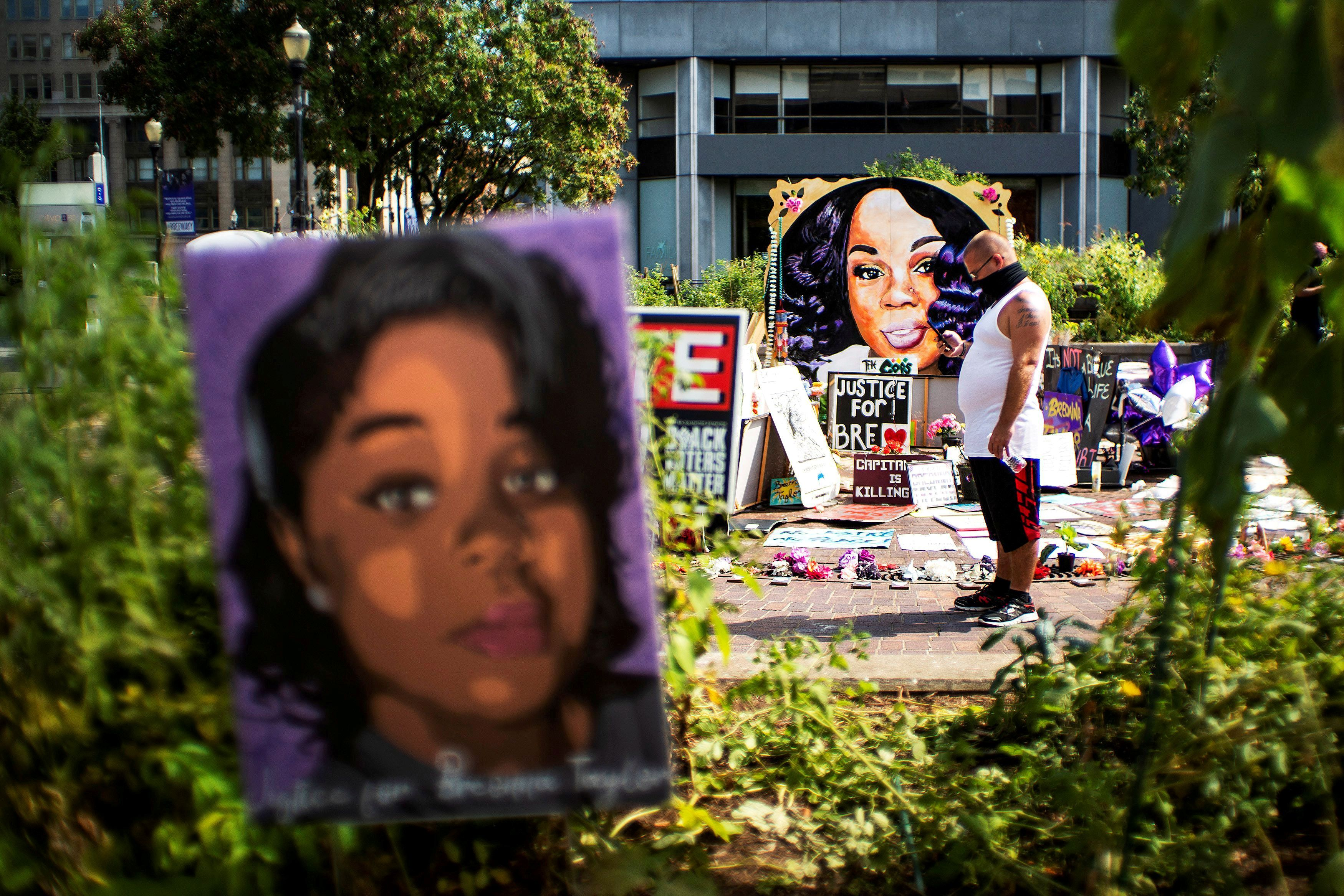 A man pauses at the memorial of Breonna Taylor before a march, after a grand jury decided not to bring homicide charges against police officers in the fatal shooting that killed her [File: Eduardo Munoz/Reuters]